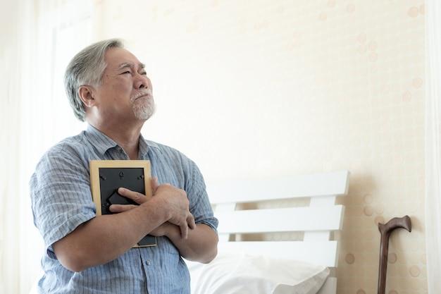 Senior homme malheureux pleure, étreint l'image de la femme décédée, rappelez-vous sa femme