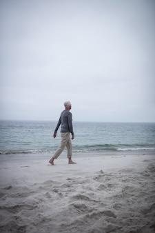 Senior homme marchant sur la plage
