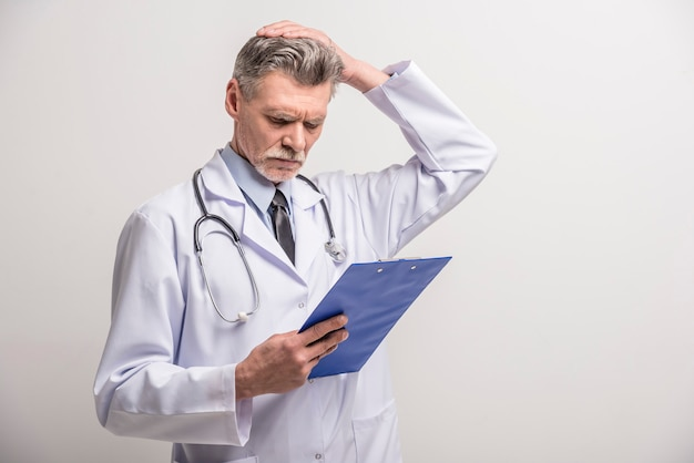 Senior homme médecin debout avec dossier