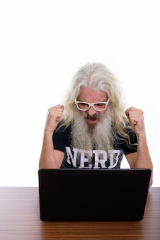 Senior homme nerd barbu à la recherche de motivation tout en utilisant un ordinateur portable