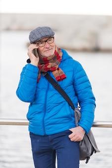 Senior homme parlant au téléphone mobile dans la rue