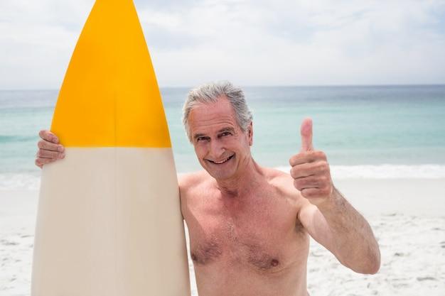 Senior homme avec planche de surf montrant les pouces vers le haut