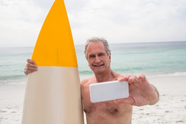 Senior homme avec planche de surf prenant un selfie sur téléphone mobile