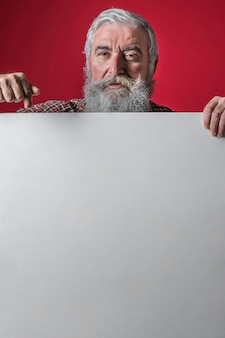 Senior homme pointant son doigt vers le bas sur une pancarte blanche vierge sur fond rouge
