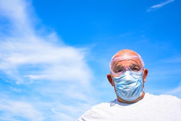 Senior homme portant un masque médical et des lunettes regardant la caméra gros plan sur un ciel bleu avec des nuages. concept de coronavirus. protection respiratoire