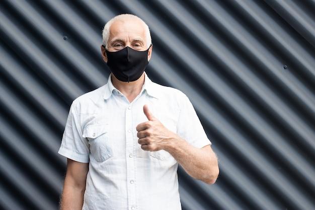 Senior homme portant un masque médical de protection montrant le geste du pouce vers le haut, place pour le texte, copyspace