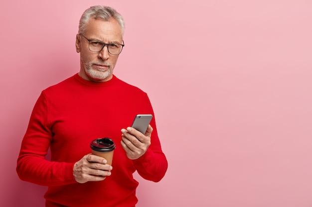 Senior homme portant un pull rouge et des lunettes à la mode