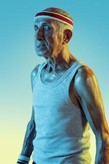Senior homme portant des vêtements de sport jouant au tennis sur gradient