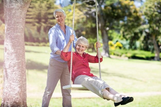 Senior homme poussant sa partenaire sur balançoire