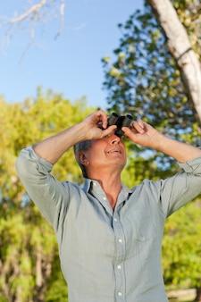 Senior homme regardant le ciel avec ses jumelles