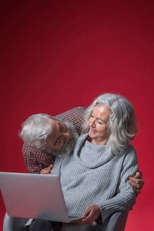 Senior homme regardant sa femme assise sur une chaise tenant un ordinateur portable ouvert sur fond rouge