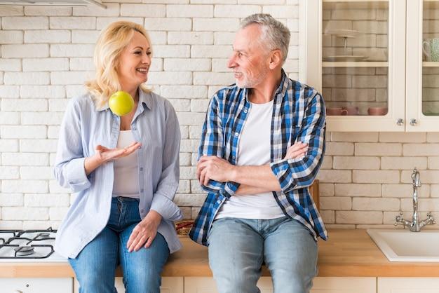 Senior homme regardant sa femme jetant une pomme verte dans la cuisine