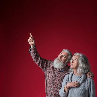 Senior homme regardant son mari montrant quelque chose à la hausse sur un fond rouge