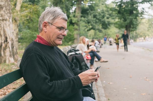 Senior homme retraité au parc, dactylographie sur mobile, expression souriante