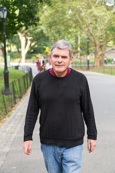 Senior homme retraité au parc, marche et détente, expression souriante
