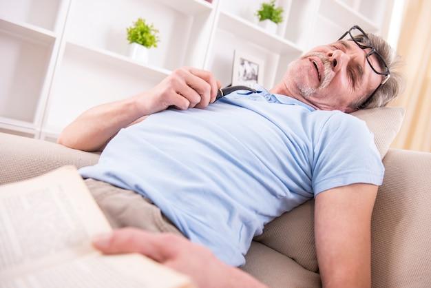 Senior homme s'est endormi alors qu'il lisait un livre.
