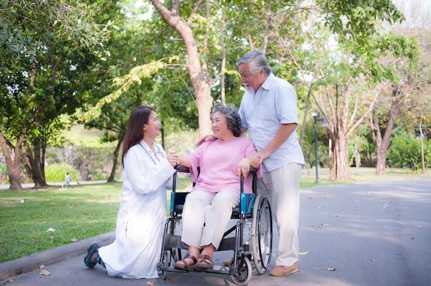 Senior homme s'occupant d'une femme handicapée dans son fauteuil roulant avec son infirmière et sa femme dans le parc.