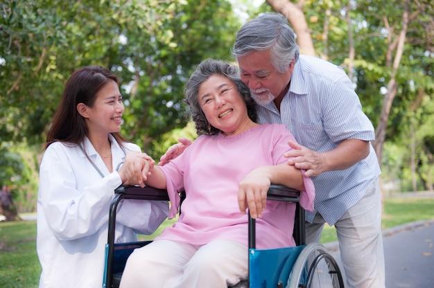 Senior homme s'occupant d'une femme handicapée dans son fauteuil roulant.