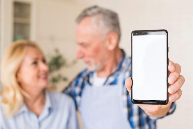 Senior homme avec sa femme montrant un téléphone portable vers la caméra, tenant dans la main