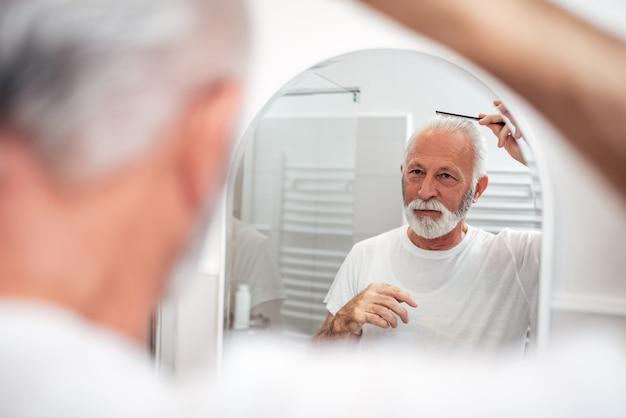 Senior homme se peigner les cheveux dans la salle de bain.