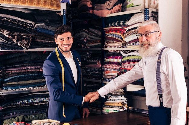 Senior homme serrant la main avec souriant jeune tailleur masculin dans son magasin