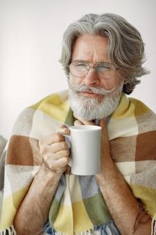 Senior homme seul assis sur un canapé. homme malade recouvert de plaid. grangfather avec une tasse de thé.