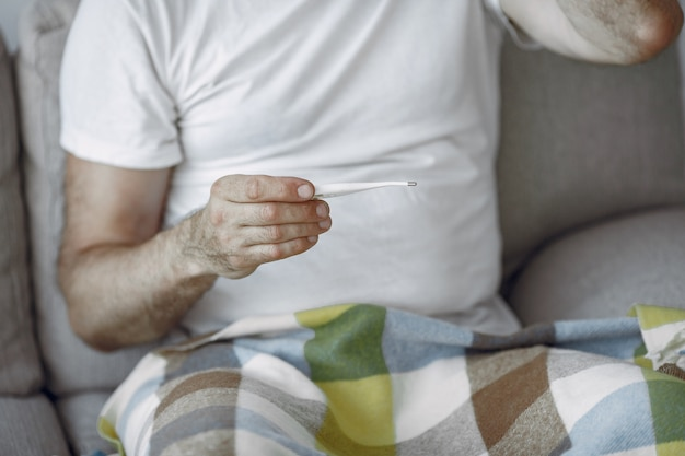 Senior homme seul assis sur un canapé. homme malade recouvert de plaid. grangfather avec thermomètre.
