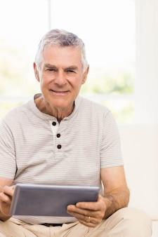 Senior homme souriant à l'aide d'une tablette sur le canapé