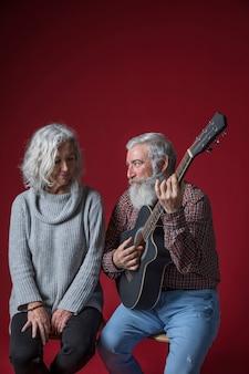 Senior homme souriant jouant de la guitare pour sa femme assise sur un fond rouge