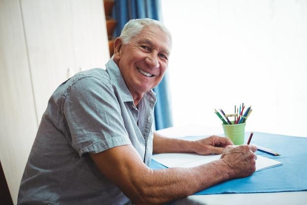 Senior homme souriant en regardant la caméra