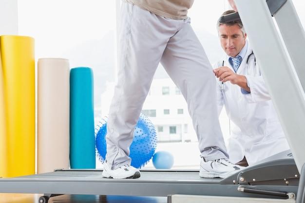 Senior homme sur tapis roulant avec un thérapeute accroupi