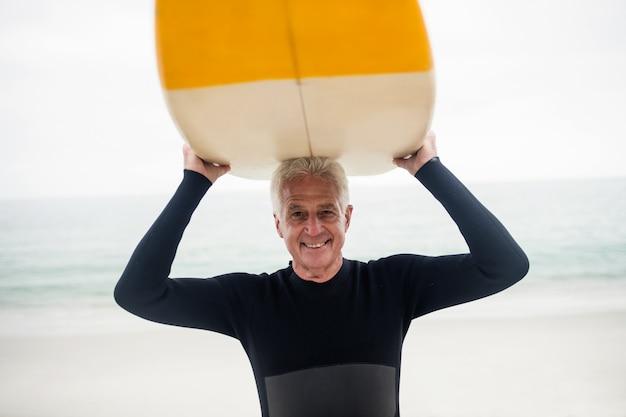 Senior homme tenant une planche de surf sur la tête
