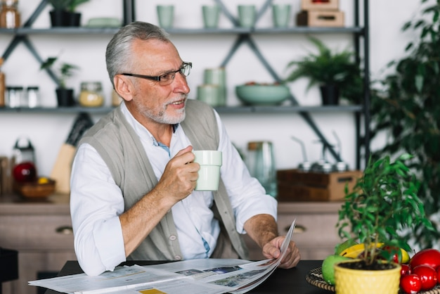 Senior homme tenant une tasse de café et journal à la recherche de suite