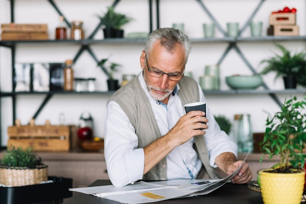 Senior homme tenant une tasse de café en lisant le journal à la maison