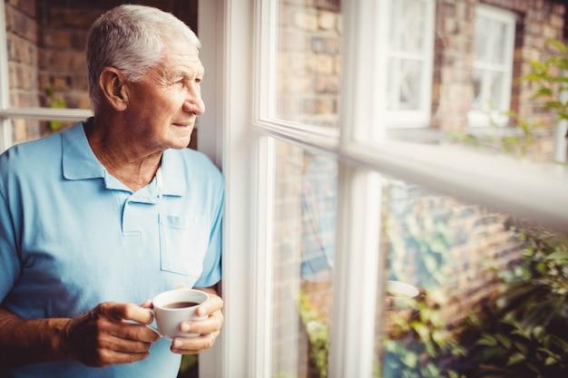 Senior homme tenant une tasse et regardant par la fenêtre à la maison