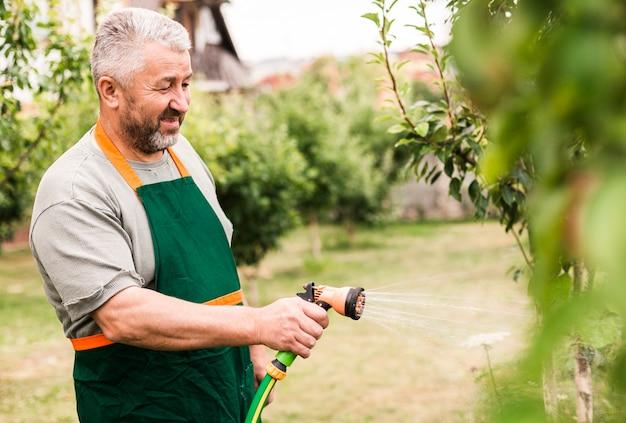Senior homme avec tuyau d'arrosage
