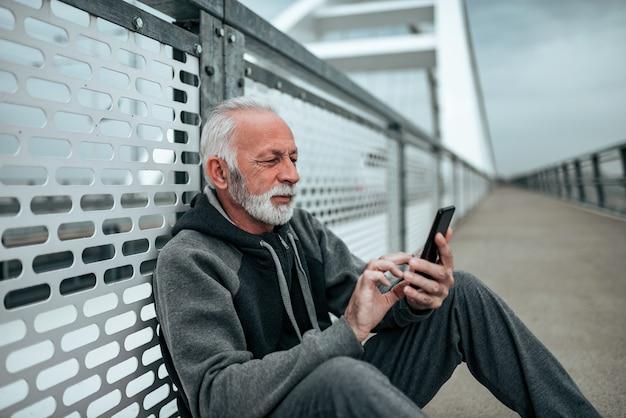 Senior homme en vêtements de sport assis sur le pont et à l'aide de smartphone.