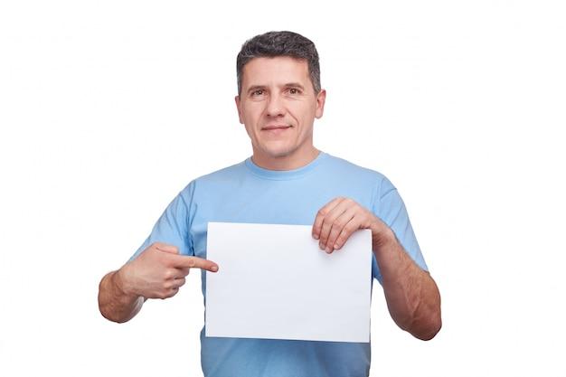 Senior homme avec visage souriant tenant un papier vierge et faisant un geste pointant son doigt vers lui.