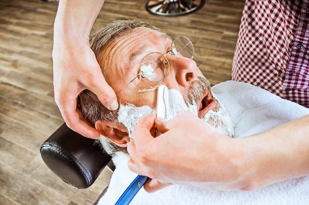 Senior homme visite coiffeur en salon de coiffure.