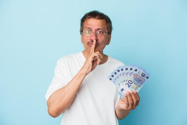 Senior indian man holding bill isolé sur fond bleu gardant un secret ou demandant le silence.