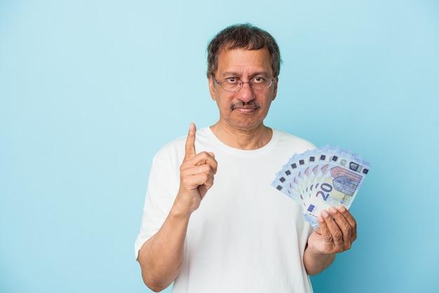 Senior indian man holding bill isolé sur fond bleu montrant le numéro un avec le doigt.