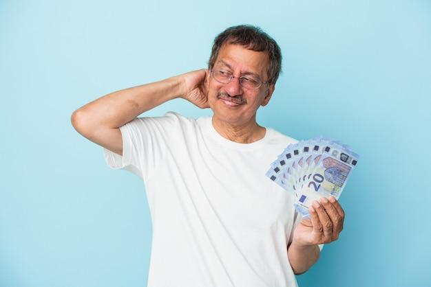 Senior indian man holding bill isolé sur fond bleu touchant l'arrière de la tête, pensant et faisant un choix.
