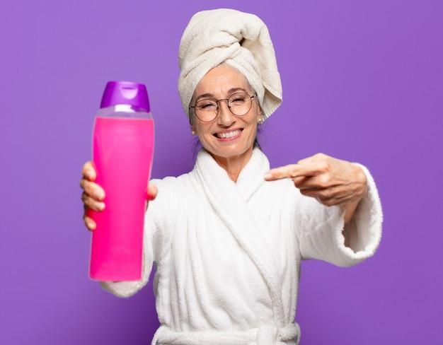 Senior jolie femme après la douche en peignoir. concept de produits de nettoyage du visage ou de douche
