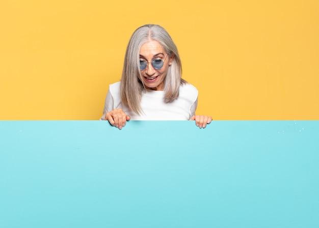Senior jolie femme portant des lunettes de soleil avec bannière bleue