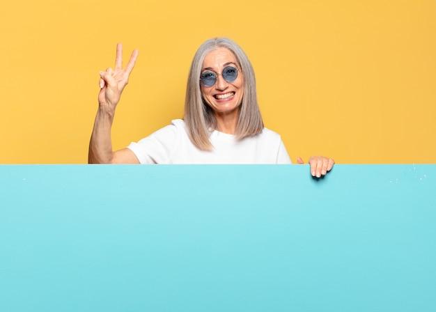 Senior jolie femme portant des lunettes de soleil avec une pancarte bleue