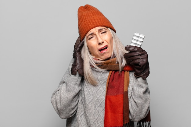 Senior jolie femme avec une tablette de pilules portant des vêtements d'hiver