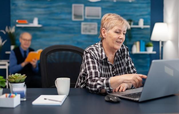 Senior lady entrepreneur travaillant et pointant sur l'écran de l'ordinateur tout en naviguant sur internet