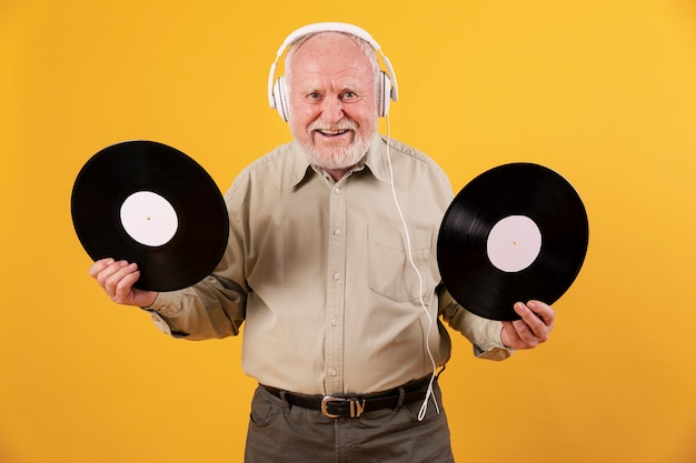 Senior à la maison heureux avec des disques de musique