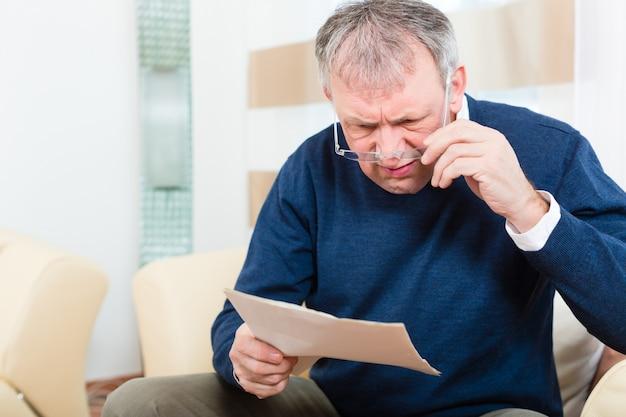 Senior à la maison reçoit un message négatif