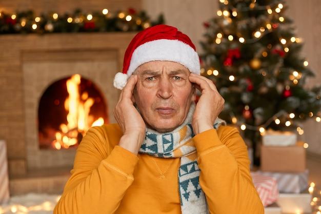 Senior male in santa hat regardant la caméra et gardant les mains sur les tempes